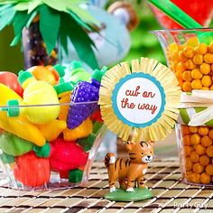 Tropical fruit candy adds pretty pops of color to a baby shower candy buffet. Click to see how we added sweet jungle-animals themed DIY details to labels & signs.