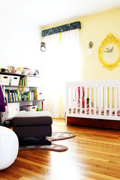 The #yellow frame and curtain #pompoms are sunny accents in this #neutral #nursery.