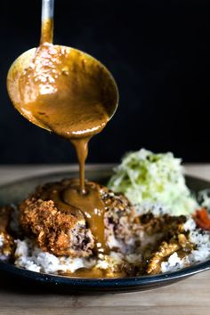 """MENCHI KATSU KARE/ HAMBURGER CROQUETTE W JAPANESE CURRY SAUCE. Deep-fried XL hamburger croquette in an elaborate panko breading, doused with a pond of lava-like Japanese curry sauce with the leading ingredient as """"clarified butter"""", then over a bed of Japanese short-grain rice with a defensive pile of shredded cabbage and pickles."""
