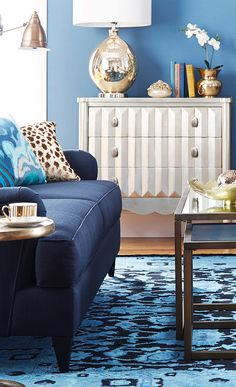 Navy couch and striped dresser with statement lamp base
