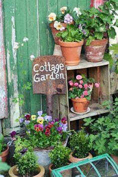Sign printed on old shovel in a vintage cottage garden display.  I have my little old snow shovel.