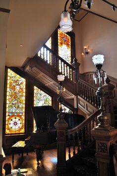 Mansion with a long wooden staircase, stained glass windows, and a grand piano in the foyer