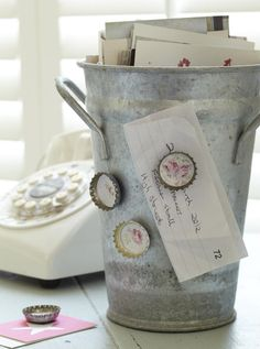 pretty...vintage bucket holds memo pads and pens, decorated bottle cap magnets holds phone messages!
