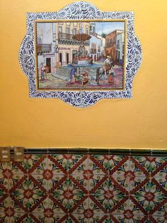 Beautiful ceramic tiles (azulejos) in my Guanajuato hotel. This handpainted scene shows a town square above with gorgeous patterned tiles on wall below. #Mexico #travel #ceramics #pottery