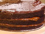 Blackout Cake: The Blackout Cake was the creation of Ebinger's, a famous New York-based neighborhood bakery chain. An indecently rich, dark tower of chocolate, this cake has become something of a Holy Grail for many bakers. Cult-like fans went through Blackout withdrawal when the bakeries closed down and The Cake disappeared. Many have tried to rec-reate this cake; I feel this version comes close. It is a multi-stepped process (remember, this was a bakery specialty) but it can easily be broken down into components.    *Ingredients    Chocolate Pudding:  1 1/2 cups milk  1/3 cup sugar  1/4 teaspoon kosher salt  2 tablespoons cocoa (preferably Dutch processed)  1 tablespoon plus 1 teaspoon cornstarch  1 egg  1 egg yolk  4 ounces semi sweet chocolate, finely chopped  1 1/2 tablespoons butter, at room temperature  *Cake:   1 1/2 cups plus 1 1/2 tablespoons all-purpose flour  3/4 cup cocoa (preferable Dutch processed)  2 teaspoons baking soda  1 teaspoon baking powder  1/2 teaspoon kosher salt  2 eggs  2 cups sugar  1/2 cup vegetable oil  1 cup buttermilk  1 cup brewed coffee, at room temperature  1 teaspoon vanilla extract  *Icing:   8 ounces semi sweet chocolate  2 1/2 tablespoons butter  1/4 cup hot brewed coffee  2 teaspoons corn syrup  1/2 teaspoon vanilla extract  3 dozen chocolate wafer cookies  *Directions   To make the Chocolate Pudding: Combine 1 cup milk with 2 tablespoons sugar in a small saucepan and bring to just under a boil.    In a mixing bowl, combine remaining sugar with salt, cocoa, and cornstarch. Whisk in remaining 1/2 cup unheated milk. Gradually whisk in hot milk and place entire mixture back into the saucepan. Heat, over medium heat, stirring, until mixture thickens and just starts to bubble.    Whisk in egg and egg yolk and cook, stirring, for 30 seconds. Remove from the heat and whisk in chopped chocolate and butter. When both are melted, strain pudding through a fine-mesh strainer, and cool. Cover with plastic and reserve in refrigerator.    **To make the Cake: Preheat oven to 350 degrees F. Lightly butter 2 (8-inch) cake pans and line with parchment. Butter the parchment and flour pans, shaking out the excess.    Sift together flour, cocoa, baking soda, baking powder, and salt. Reserve.    In a mixer with a whip attachment, beat eggs and sugar until thick and lemon-colored. Beat in vegetable oil. Alternately add dry ingredients with buttermilk, scraping the bowl once or twice. Add the coffee and vanilla to form a thin batter. Divide between prepared cake pans.    Bake until a toothpick inserted in the center of a cake comes out clean, about 40 to 45 minutes. Cool in pan for 15 minutes. Invert onto cooling racks, peel off paper and cool completely.    ** chocolate with butter. Remove from heat, whisk in brewed coffee, corn syrup, and vanilla. Place icing over an ice bath and chill, whisking often until the mixture is of soft but a spreadable consistency. Working quickly, ice the sides and top of cake.    In a food processor, pulse the cookies into crumbs. Press the crumbs onto sides and top of cake.    Serve cake at room temperature. If holding for more than 2 hours, store in refrigerator for up to 48 hours, but bring to room temperature before serving.    Serving Suggestion: Blackout cake is meant to be served simply, on its own. If you want to dress individual plates, perhaps add a drizzle of fudge sauce and a sprinkle of cocoa powder