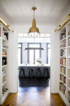 herringbone floors, built-in bookcases, brass lighting