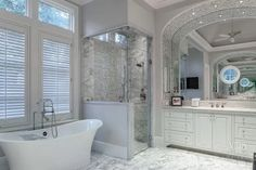 LOVE so much about this bathroom - the tub, the shower, the arch around the sink, the tiling, the light and bright airiness about the room, etc!