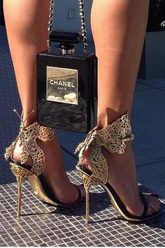 Sergio Rossi black and gold butterfly heeled sandals with Chanel perfume bottle clutch.