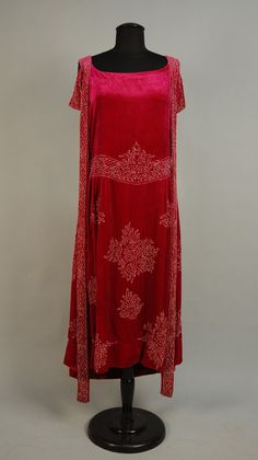Crystal beaded raspberry velvet dress, 1920s. From the estate of actress Dolores Costello Barrymore (grandmother of actress Drew Barrymore). Unusual dress with strap cap sleeve and long loop that circles from shoulder around hem. Via Charles A. Whitaker Auctions.
