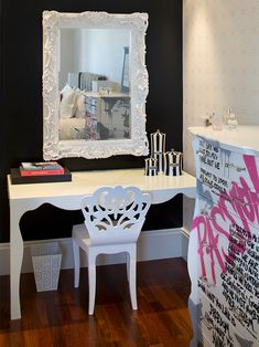 Black walls, ornate white mirror. Funky laquered desk with fun, cutout desk chair. Curvy dresser covered in graffiti.