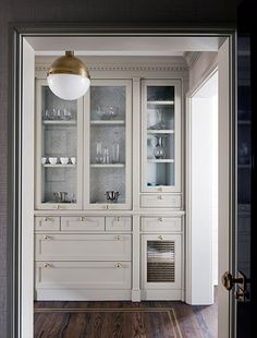 Courtney Hill Interiors - Butler's pantry, glass fronted cabinet with wallpapered cabinet interior, gray kitchen cabinets with brass hardware, brass and opalglass Hicks pendant,