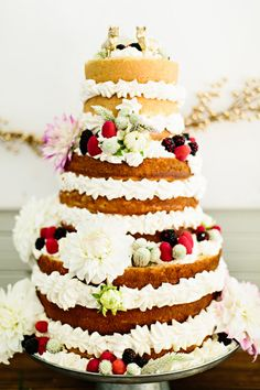 naked cake with berries, photo by Emily Chidester http://ruffledblog.com/fort-mill-barn-wedding #cakes #weddingcake #dessert