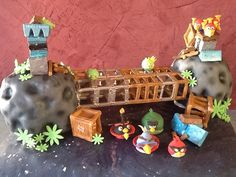 Two Cakes of Different Flavors. Devil's Food Cake with Rasberry Curd Filling, Covered in Chocolate Chili Ganache and Finished in Fondant. The Asteroids are Sweet Rolls Covered in Chocolate Chili Ganache. The Buildings are Blocks of Chocolate and the Angry Birds are Fondant.