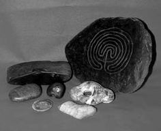 Working Stones    From left, back row: Large ancient whet-stone, the Troy stone employed within the Cornish Craft to aid the inducing of useful trance states. Mid row: A stroking stone, a Cornish Witch-tool for healing magic and two hag stones. Front row: pre-historic flint cutting/scraping tool and a stone of quartz employed to amplify the serpentine land powers within the working Circle. stone