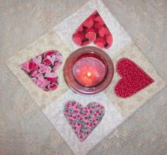 Heart Applique Quilted Candle Mat. Looking for a beautiful and simple to make Valentine's Day decoration? This Heart Applique Quilted Candle Mat delivers a handmade decoration you'll love. It only requires fabric scraps so dive into your stash and create this lovely quilted project today. This would also make for a wonderful gift for teachers, neighbors and friends. Make several and spread the Valentine's Day cheer this holiday.