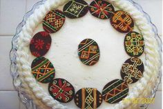 Pysanka cake - melt chocolate and spread thinly on wax paper, let set, cut out eggs with cookie cutter. Make designs with buttercream icing. By Lada Onyshkevych.