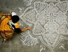 """Kolams are geometrical line drawings composed of curved loops, drawn around a grid pattern of dots. Female Hindu family members paint them in front of their homes. It is a sign of invitation to welcome all into the home."""