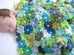Lovely crochet flower blanket - made by several women using 27 shades of blue and green yarn.