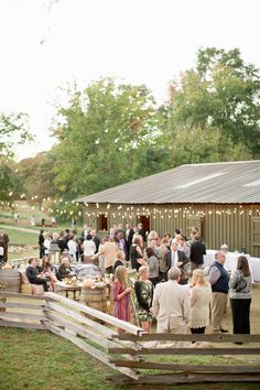 Love this outdoor receptions with hay bale seating and whiskey barrels as cocktail tables.