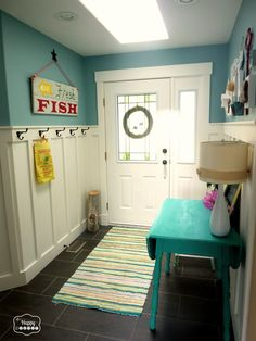 Front door - Aegean Teal by Benjamin Moore Board and batten and all trim work throughout - Cloud White by Benjamin Moore Hallway walls above the board and batten - Colorado Gray by Benjamin Moore