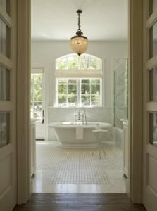 chic, elegant master bathroom design with crystal chandelier, spa soaking tub, white carrara marble basketweave tiles, silver tripod accent table, glass shower and ivory roman shades. Elegant, timeless bathroom.