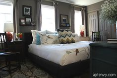 Bedroom painted in deep rich taupe gray brown, upholstered headboard, mid-century and vintage accents to make eclectic space. King bed has Dwell Studio chinoiserie duvet set.