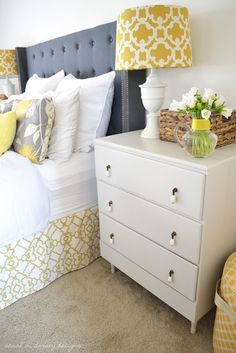Gray & yellow bedroom with gray tufted headboard and yellow printed lamp