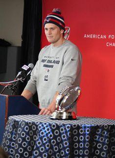 Tom Brady wearing a striped snow hat, navy - red & white, flying elvis logo and pom pom.