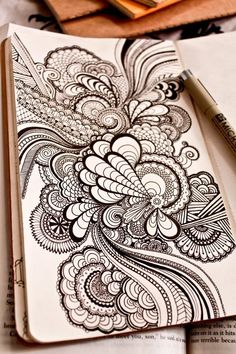 The drawing shows myriad curvilinear lines of varying thickness and direction.  These lines give the forms definition. journal, sketch, pattern, doodle, art, tattoo ink, drawing, design, mandala tattoo