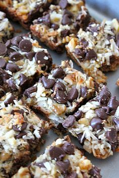 Magic Cookie Bars 1/2 cup butter, melted 1 1/2 cup graham cracker crumbs 1 (14 ounce) can Eagle Brand Sweetened Condensed Milk 2 cups semisweet chocolate chops 1 1/3 cups flaked coconut 1 cup chopped nuts  Preheat over to 350 degrees Fahrenheit.  Coat a 9x13 baking pan with no-stick cooking spray.