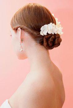 Peinado de novia recogido y de lado con un tocado florar de moda en 2013 - Foto Brides Facebook