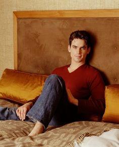 matt bomer in a red shirt in a bed