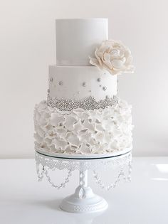 White wedding cake with ruffles and silver edible beads.