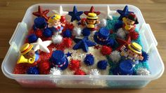 Fourth of July Sensory Bin - It contains pom poms, patriotic hats, star shaped jewels, glittery foam stars, patriotic little people and dyed rice (rice dyed with kool aid for the added sense of smell) - Preschool Activity