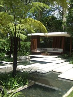 A modern simplistic outdoor room. Though super modern creates the feel of relaxation and tranquility a tropical balinese garden can give. The dark timber slats and white rectangular  stepping stones are well balanced with the ferns and tropical plants not usually found in modern landscaped gardens and outdoor rooms.