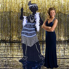 This All That Jazz Flapper Standee is a black cardboard standee that resembles a woman from the 1920s wearing a feathered headband and frilly dress. Each cardboard one-sided 1920s Flapper Standee is free-standing measuring 6 feet 2 inches high x 2 feet 10 inches wide and requires easy assembly.