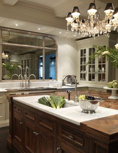 Love this marble sink/prep area inset into this gorgeous parquet wood top- Mirror instead of window over sink- designed by Julie Charbonneau