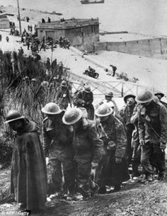British prisoners of war captured at Dunkirk, France, in June 1940 walk dejectedly up a hill near a German fortification