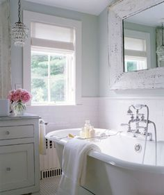 Shabby chic cottage bathroom!    Marble countertops counter tops and glass crystal light pendants! How chic and pretty is this bathroom? Claw foot tub, white bathroom cabinets, white washed vintage wood mirror and white roman shade with gray border piping! Blue green bathroom. blue green paint wall color. Blue green gray pink bathroom colors.