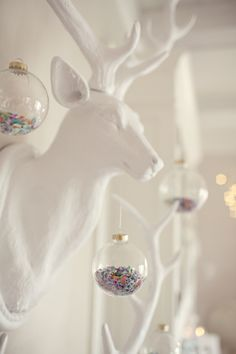 A modern Christmas: Not a stich of red or green in sight.  A gold tinsel tree, ornaments filled with confetti, Carnations mixed with Peonies, oversized deer (including a hunting decoy painted white and covered in lights), and glasses overflowing with champagne.