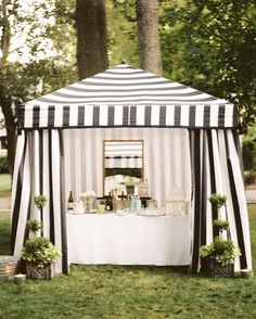 A black-and-white-striped pavilion at an outdoor dinner party.