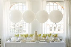 Simply using four oversized balloons can add some pizazz to your food table. dessert tables, wedding ideas, dessert buffet, food stations, party bars, white weddings, cake tables, dessert bars, baby showers