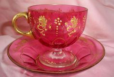 ANTIQUE CRANBERRY ENAMELED SCROLL WORK FOOTED CUP & SAUCER