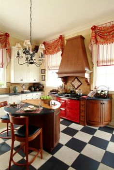 Retro blends with French Country in this bright and charming kitchen, with its custom window treatments, red Aga cooker, and dramatic black and white checkerboard floor.  (viaK.Marshall Design Inc.)