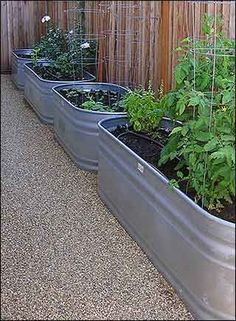 DIY Trough Vegetable Garden Tutorial - made from galvanized water tank / trough. Drill holes in bottom. Layer the following, mesh liner (keeps soil from draining out), rocks or plastic bottles (create drainage space), top with soil