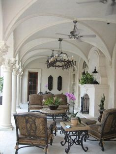 gorgeous veranda with a fireplace... great use of wrought iron