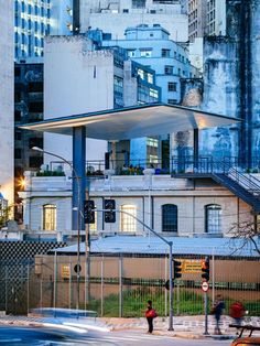 A slender steel awning shades artists from the sun on the rooftop of this creative arts space.