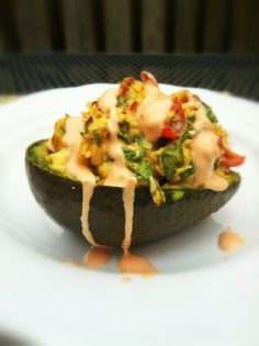 healthy, clean, and low-carb: spicy chicken, spinach  tomato stuffed avocado with a sriracha-greek yogurt sauce