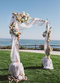 Such a romantic wood arch draped in white fabric and flanked by beautiful floral arrangements.
