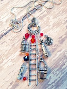 "'Hot Stuff""  Firefighter Charm Necklace  (includes six Tibetan silver tone and pewter charms: a ladder, a firetruck, a fire extinguisher, a moving bucket, a fire hydrant and a hose hang from an  bail with Swarovski accents on a 17"" silver plated ball chain) 